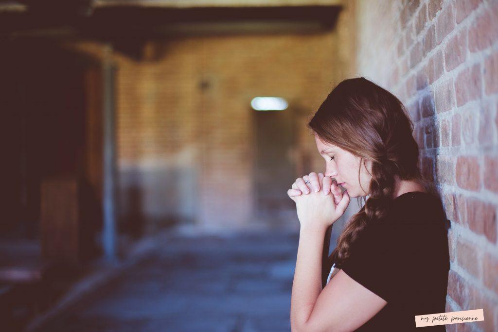 jeune fille stressée appuyer sur un mur de brique